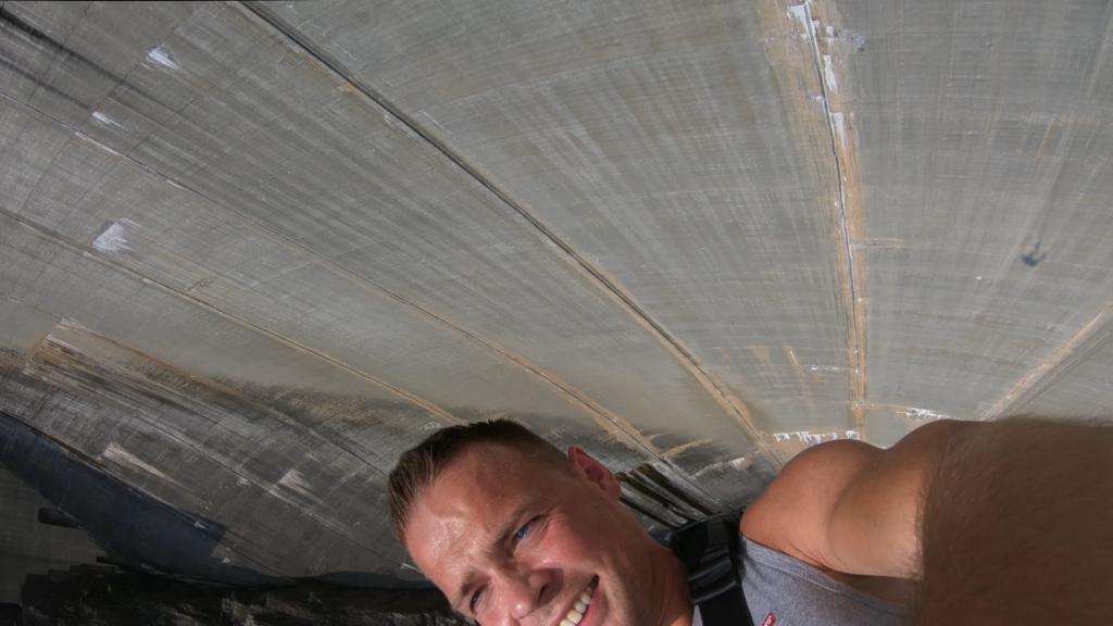 twarz na tle betonowej ściany tamy Verzasca