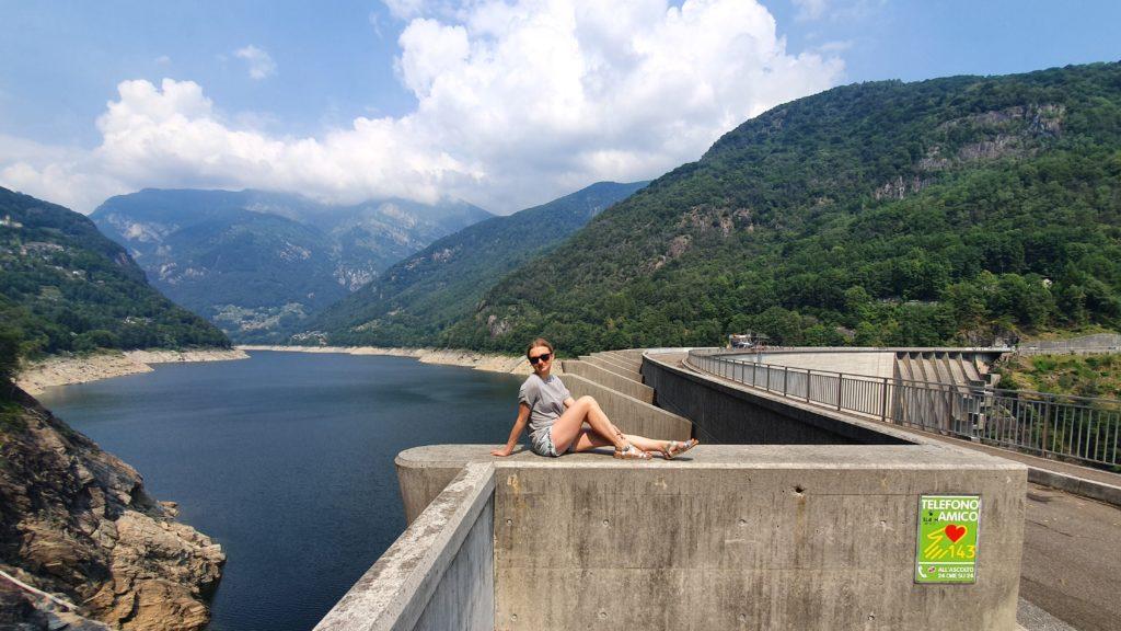 dziewczyna siedząca na murze tamy contra