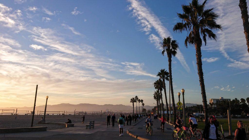 Spacerujący ludzie po Ocean Boardwalk w Santa Monica o zachodzie słońca