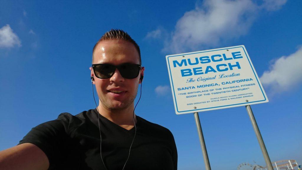 Człowiek na tle znaku Muscle Beach