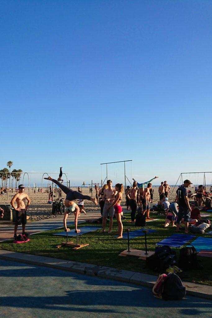 Grupa sportowców trenująca na plaży Muscle Beach w Santa Monica