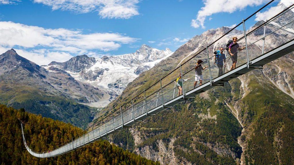 ludzie spacerujący przez górski most