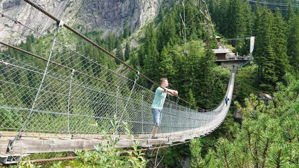 Człowiek stojący na wiszącym moście. Najlepsze Alpejskie mosty