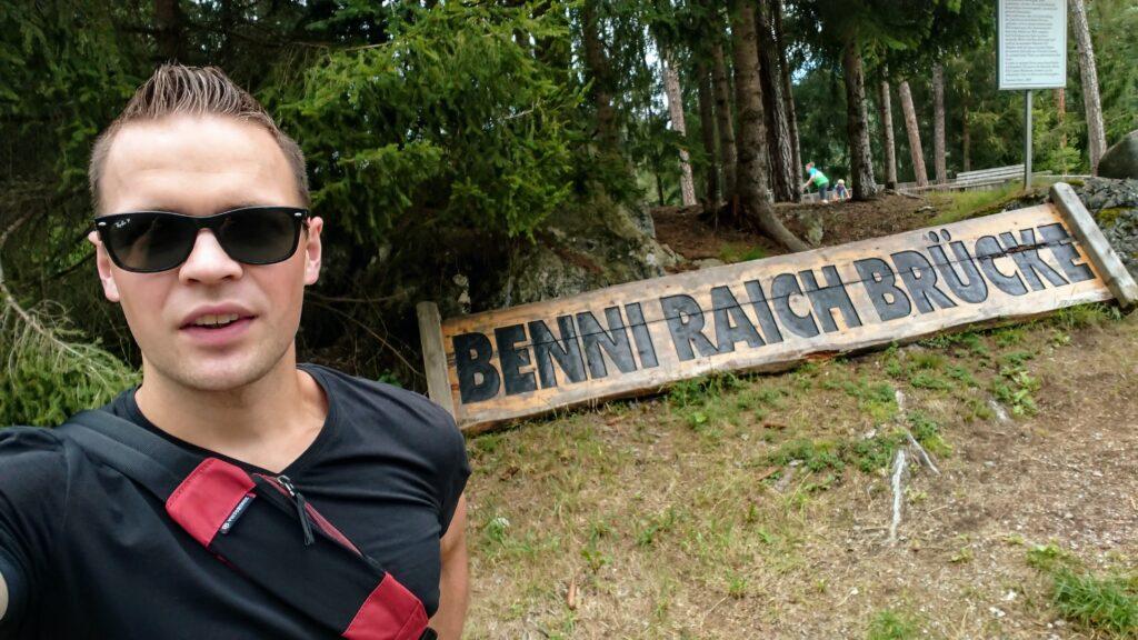 Człowiek na tle napisu Benni Raich Brücke