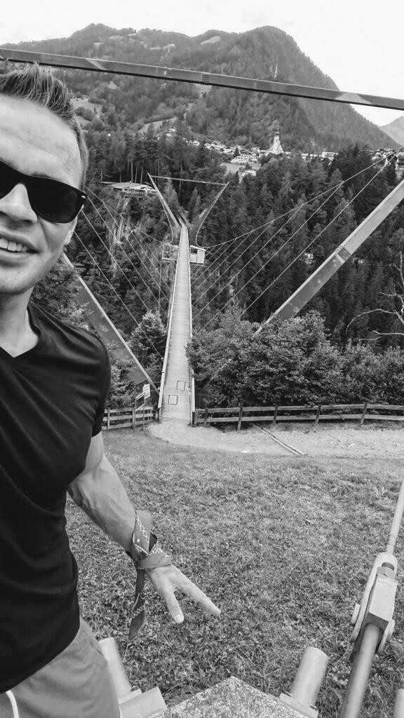 Czarno białe zdjęcie mężczyzny przed kładką dla pieszych w górach