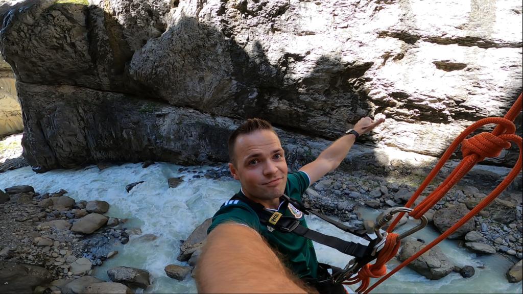człowiek bujający się na linie w kanionie nad rzeką