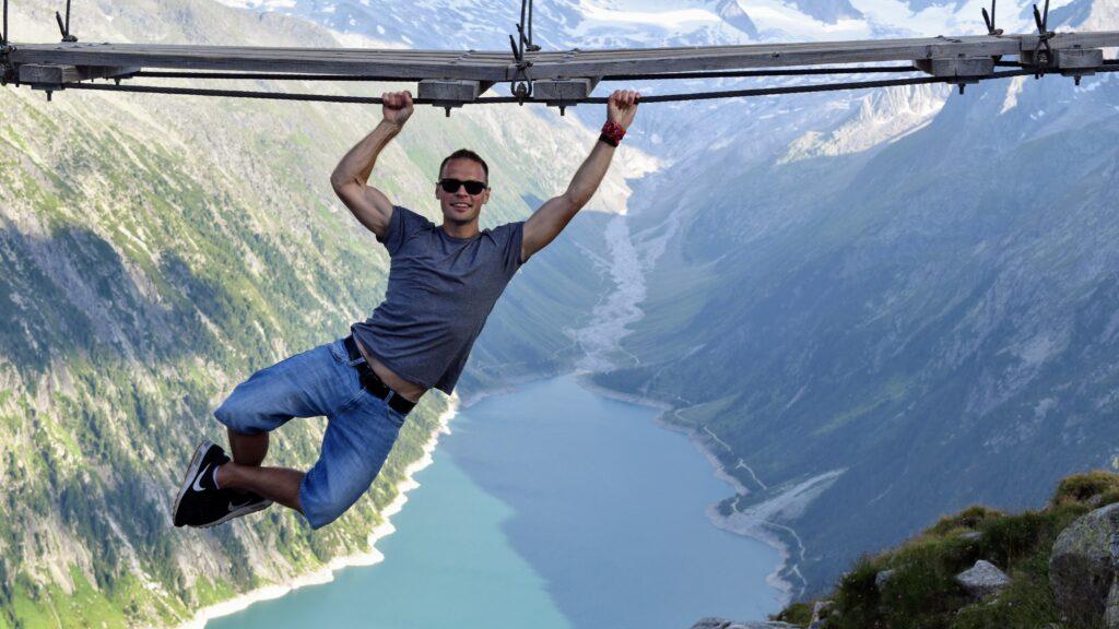 Człowiek zwisający pod mostem w górach. Najlepsze Alpejskie mosty