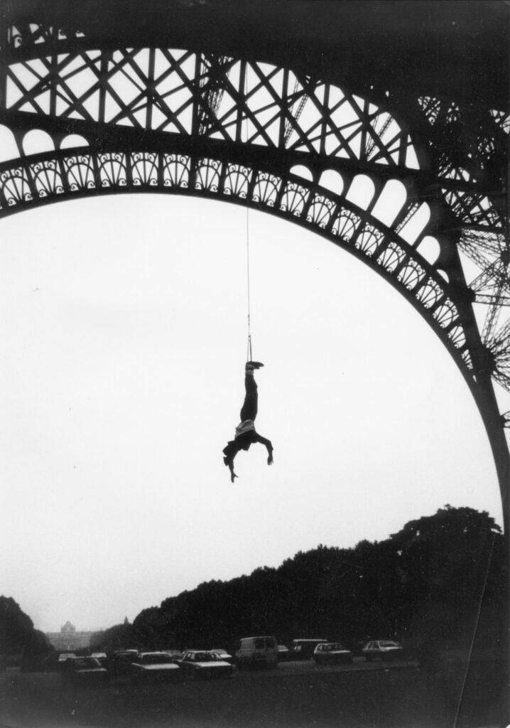 Mężczyzna zwisający na linie z wieży eiffla